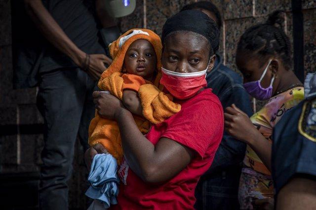 Una mujer de Haití espera con su hijo para pedir asilo en la capital de México, Ciudad de México
