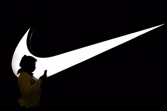 """Archivo - FILED - 01 July 2020, Indonesia, South Jakarta: A woman walks past an illuminated logo of the """"Nike"""" brand at Die Pondok Indah Mall. Sports apparel firm Nike has surpassed market expectations with its figures for the last quarter. At 12.35 billi"""