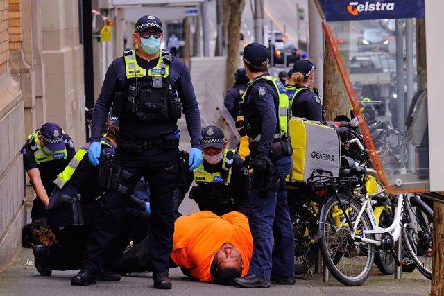 La Policía de Australia detiene a un manifestantes durante las protestas de Melbourne.