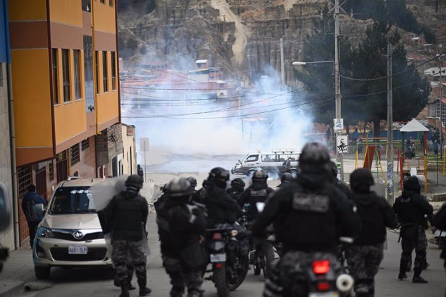 21 September 2021, Bolivia, La Paz: Police use tear gas against coca farmers in front of a hospital. A coca farmer leader had been injured by rival groups and admitted to hospital. Photo: Radoslaw Czajkowski/dpa