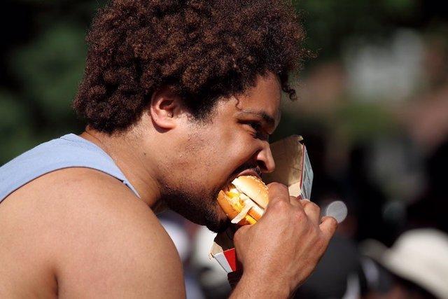 Archivo - Hombre comiendo una hamburguesa en la calle.