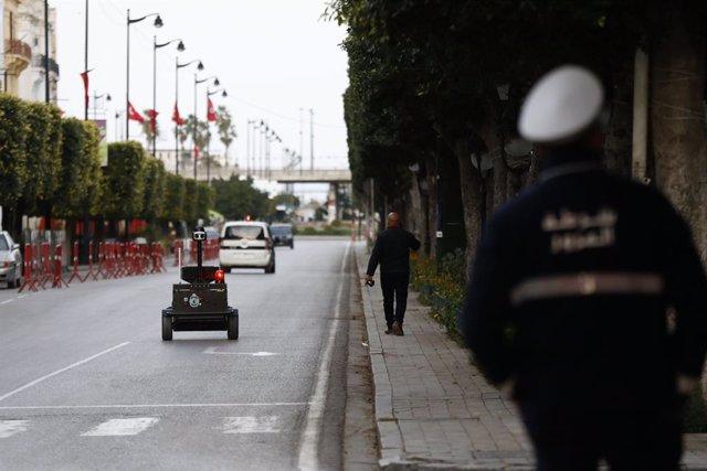Archivo - Un policía en Túnez junto a un robot encargado de comprobar si se cumple el confinamiento por coronavirus