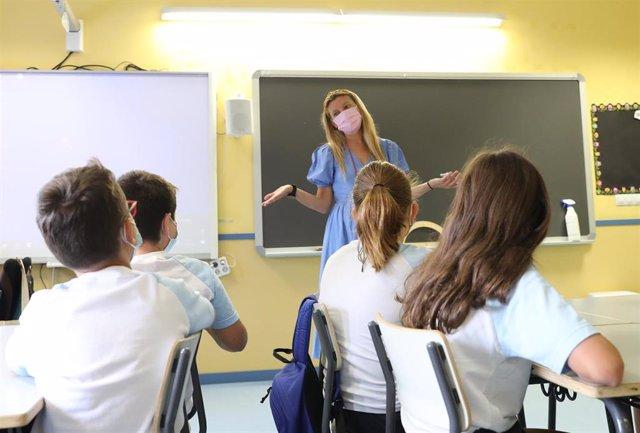 Una profesora con un grupo de niños en una de las aulas del colegio Maestro Padilla