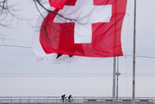 Archivo - Ciclistas junto a una bandera de Suiza en Basilea