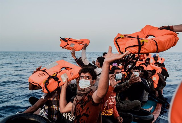 Archivo - HANDOUT - 04 July 2021, Italy, ---: Migrants in a small boat take life jackets from the helpers as they sit in a small boat in the Mediterranean Sea. The Ocean Viking rescue vessel has pulled 67 people from the central Mediterranean Sea, SOS Med