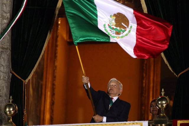 15 September 2021, Mexico, Mexico City: Mexican President Andres Manuel Lopez Obrador waves the Mexican national flag during the ceremony of the Grito de Independencia (the Cry of Independence) from the National Palace on the eve of the Independence Day o