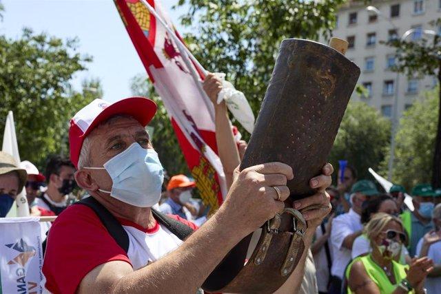 Archivo - Un manifestante en la calle, sosteniendo un cencerro, frente a la sede del Ministerio para la Transición Ecológica y el Reto Demográfico para protestar por la inclusión del lobo en el Listado de Especies Silvestres en Régimen de Protección Espec