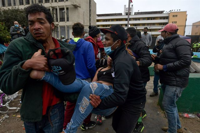 24 September 2021, Chile, Iquique: Migrants carry a woman who fainted during an operation by security forces. Security forces evicted migrants from a place where they were living in tents. Photo: Cristian Vivero Boornes/Agencia Uno/dpa