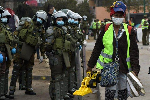 Forces de seguretat xilenes vigilen el desallotjament d'un campament de migrants veneçolans en Iquique