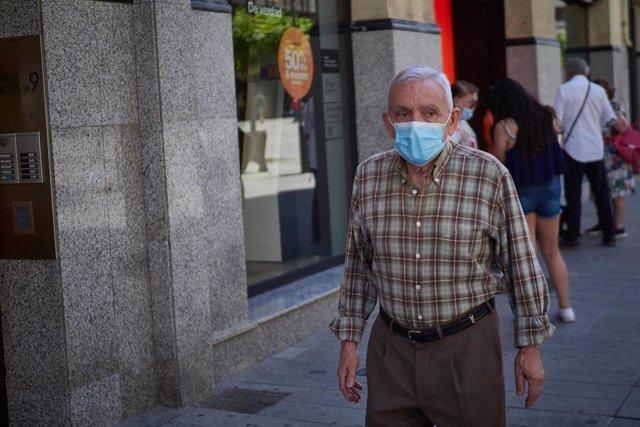 Archivo - Un hombre protegido con mascarilla pasea.