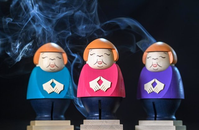 22 September 2021, Saxony, Seiffen: A picture made available on 24 September 2021 shows three incense burner figurines of German Chancellor Angela Merkel doing her trademark hand gesture at the Seiffener Volkskunst workshop. The Merkel-themed burners have