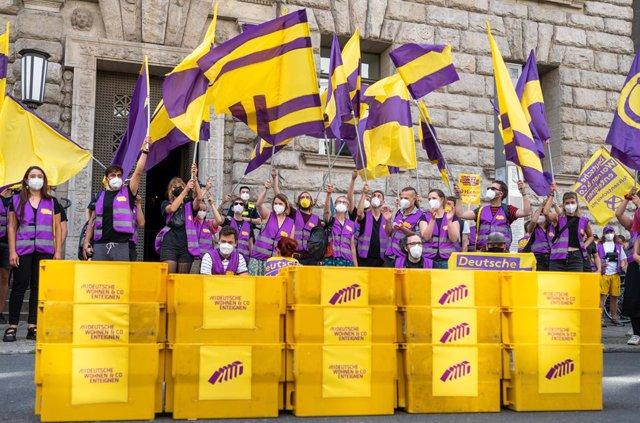 """Archivo - 25 June 2021, Berlin: Supporters of the initiative """"Expropriate Deutsche Wohnen & Co."""" wave flags as they bring boxes with collected signatures for a referendum on the expropriation of large real estate companies to the Senate Department for the"""