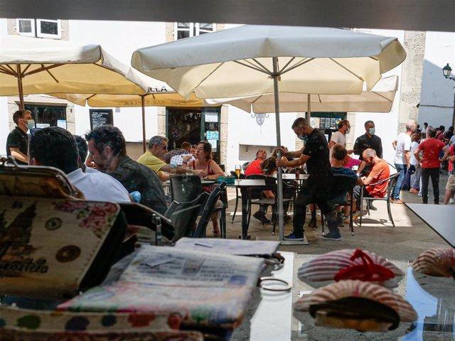 Archivo - Varias personas en la terraza de un restaurante en Santiago.