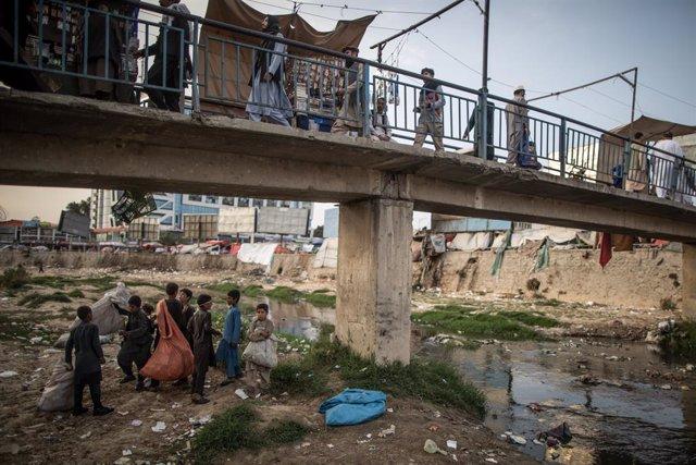 Jóvenes afganos recogen plástico y otros materiales en el río de Kabul para venderlos de cara a su reciclaje en Afganistán