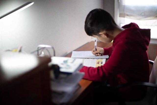 Archivo - Un niño realiza sus deberes en su habitación.