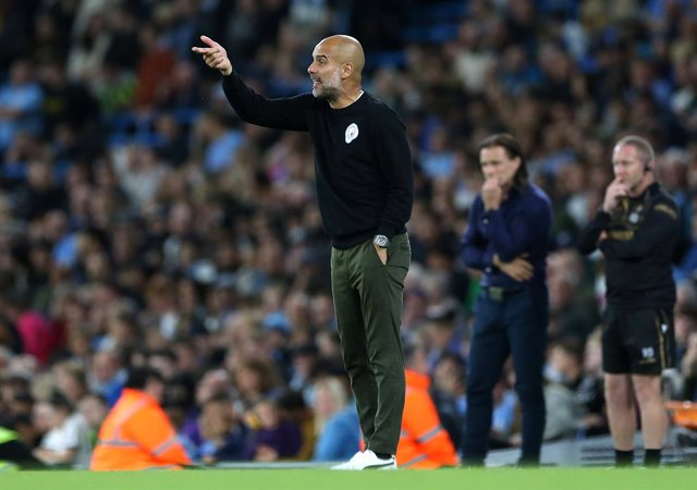 21 September 2021, United Kingdom, London: Manchester City manager Pep Guardiola instructs his players as Wycombe Wanderers' Gareth Ainsworth looks on during the English Carabao Cup third round soccer match between Manchester City and Wycombe Wanderers at