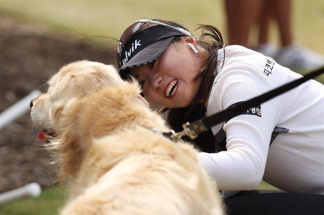 Una mujer coreana junto a un perro