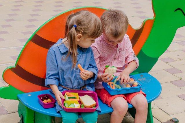 Archivo - Niños comiendo frutas y verduras
