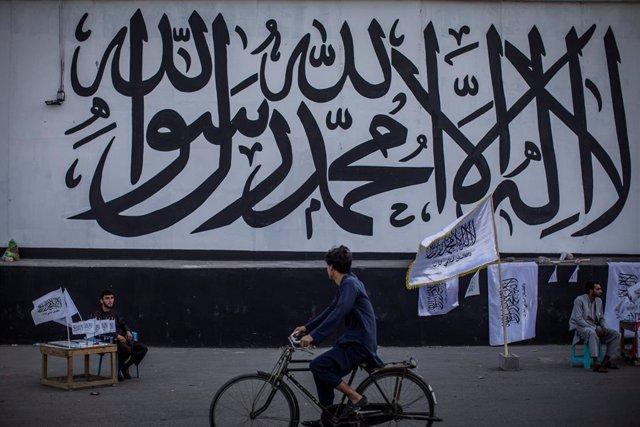 Un hombre vende banderas de los talibán frente al muro de la antigua Embajada de EEUU en la capital de Afganistán, Kabul, ahora cubierta con un mural religioso