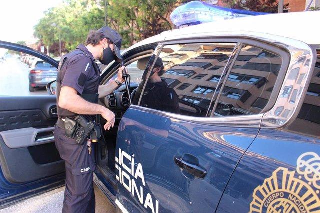 Un agente junto a un coche patrulla