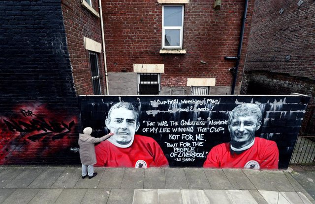 Archivo - FILED - 02 March 2021, United Kingdom, Liverpool: A woman touches a mural of Ian Saint John, who passed away on Tuesday, depicting him alongside his strike partner and World Cup hero Roger Hunt. Photo: Peter Byrne/PA Wire/dpa