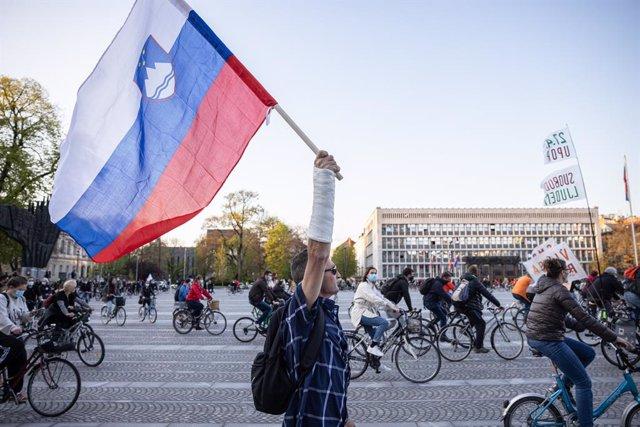 Archivo - 23 April 2021, Slovenia, Ljubljana: A protester carries the Slovenian flag during an anti-government protest. Photo: Luka Dakskobler/SOPA Images via ZUMA Wire/dpa