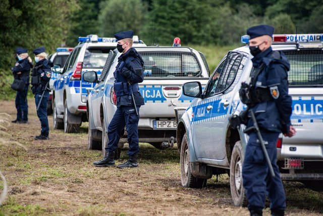 01 September 2021, Poland, Usnarz Gorny: Police officers stand on guard next to the village of Usnarz Gorny near a makeshift camp where a group of migrants stay and are not being let into the Polish side. The Polish government is introducing a State of Em