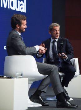 El presidente del PP, Pablo Casado (i) y el expresidente de Francia Nicolas Sarkozy (d), durante la mesa titulada 'La sociedad abierta y sus enemigos', en el marco de la tercera jornada de la Convención Nacional del PP, a 29 de septiembre de 2021, en Madr