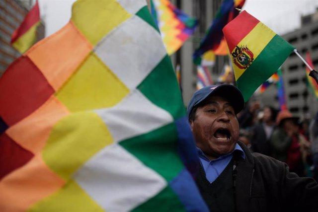 """Archivo - Un simpatizante del expresidente boliviano Evo Morales  sostiene la bandera """"wiphala"""", que representa al pueblo indígena de la nación."""