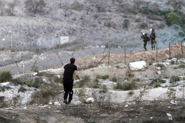 Un joven palestino lanza piedras contra dos agentes de las fuerzas de Israel en una imagen de archivo.