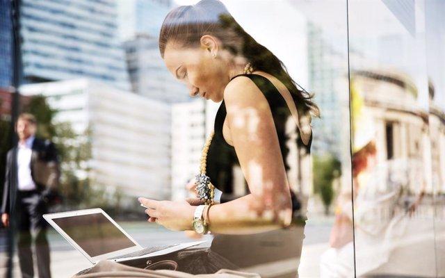 Archivo - Mujer conectada a WiFi con un ordenador y un móvil.