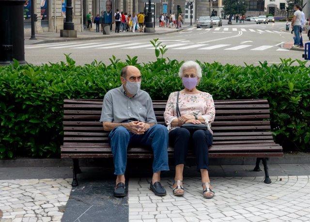 Archivo - Pareja de ancianos con mascarillas sentados en un banco de Oviedo durante el verano de la pandamia del covid 19. Oviedo a 25 de agosto del 2020