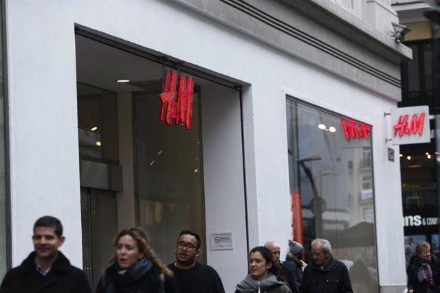 Archivo - Personas paseando por delante de la tienda H&M