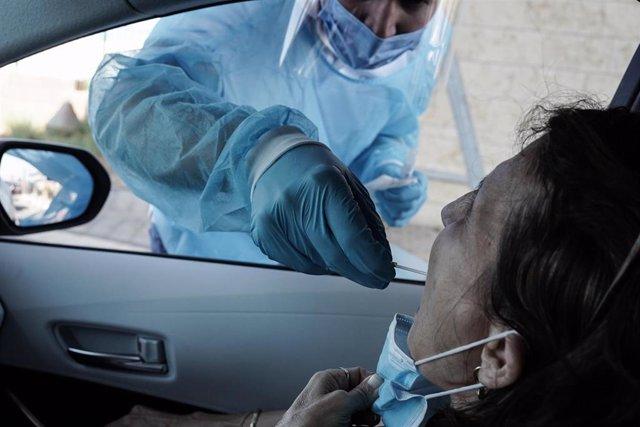 Un sanitario practica una prueba PCR a un ciudadano.