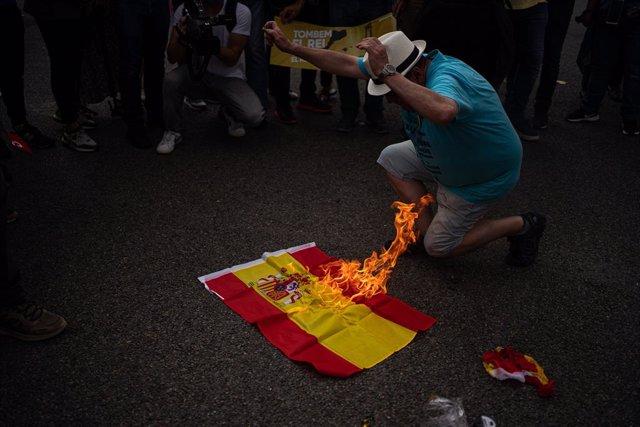 Queman banderas de España durante la protesta contra Felipe VI en Barcelona.