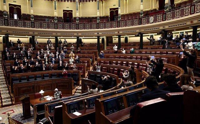 Archivo - Miembros del hemiciclo aplauden durante una sesión plenaria en el Congreso de los Diputados, Madrid, (España), a 18 de marzo de 2021. El pleno estará marcado, entre otras cuestiones, por el proyecto de Ley de medidas urgentes de prevención, cont