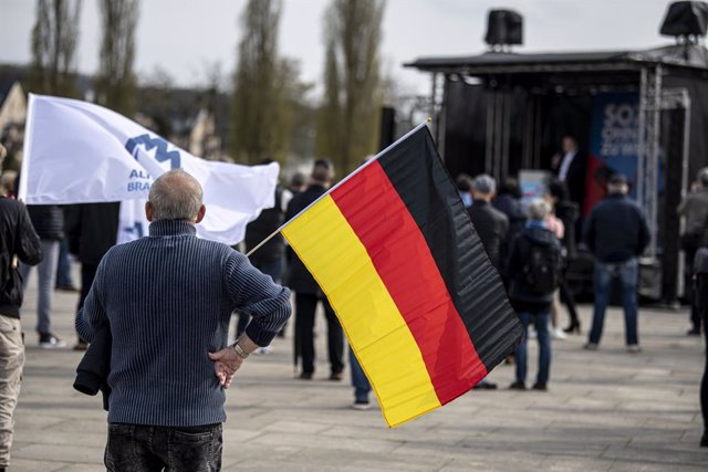 """Archivo - 01 May 2021, Brandenburg, Potsdam: A man with a German flag stands at the demonstration of the AfD on Labour Day under the motto """"Social instead of turning red"""". Photo: Fabian Sommer/dpa"""