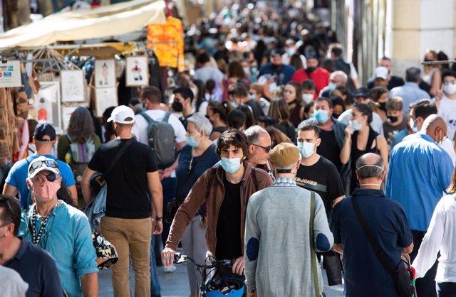 Visitantes pasean por El Rastro, a 26 de septiembre de 2021, en Madrid (España). El tradicional mercadillo madrileño de El Rastro vuelve este domingo a la normalidad pre pandemia con el 100 por ciento de vendedores autorizados y con las medidas de segurid