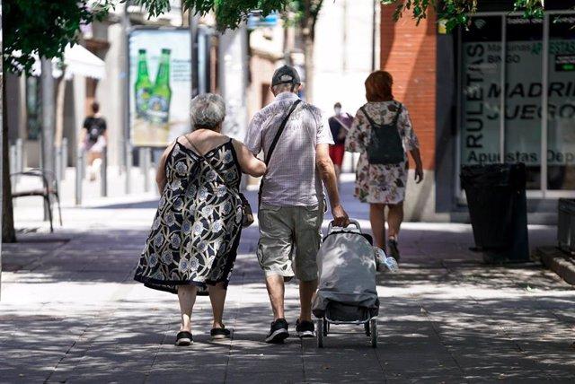 Archivo - Una pareja de personas mayores camina por la calle con un carro de compraen Madrid, (España).
