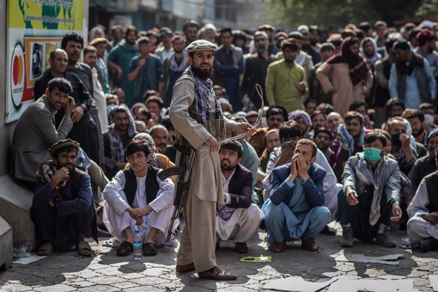 FILED - 22 September 2021, Afghanistan, Kabul: A Taliban security guard plays with a whip while standing in front of Afghan men waiting outside a bank to withdraw money. Photo: Oliver Weiken/dpa