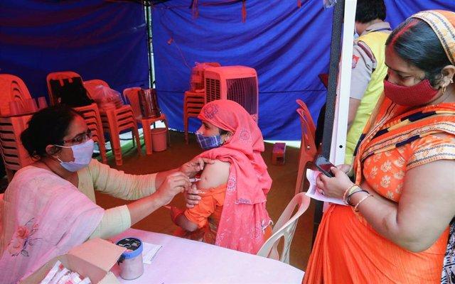 Inoculan con Covaxin a una mujer en un campo de vacunación cerca del edificio de la Organización Mundial de la Salud en Nueva Delhi.