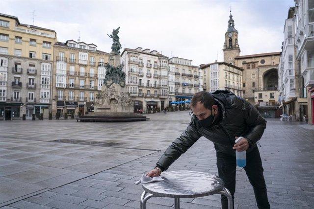Archivo - Un camarero limpia una mesa de la terraza de su cafetería durante una jornada marcada por la reapertura de los establecimientos en los municipios vascos pertenecientes a la 'zona roja', en Vitoria, Álava, País Vasco, (España), a 10 de febrero de