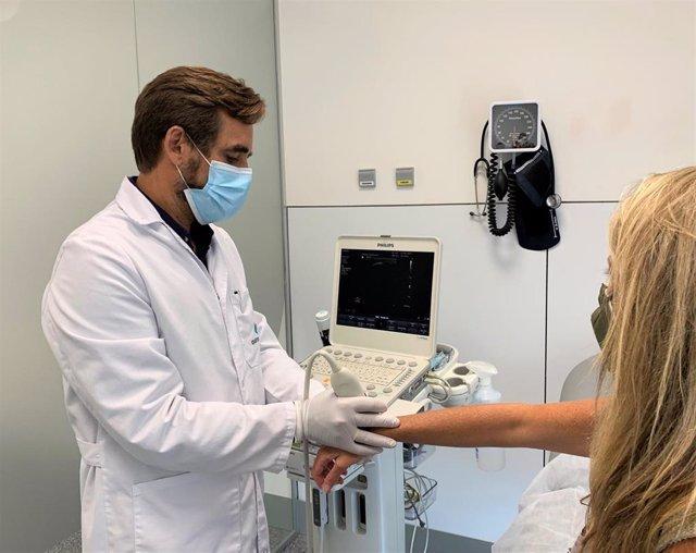El jefe de servicio de Reumatología del Hospital Quirónsalud Córdoba, Manuel Romero, realiza una ecografía a una paciente en consulta.