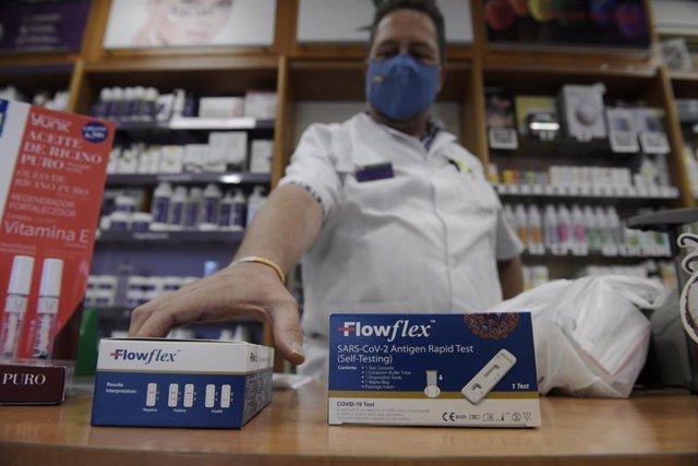 Archivo - Un farmacéutico enseña un test de antígenos de detección del COVID-19 en una farmacia.