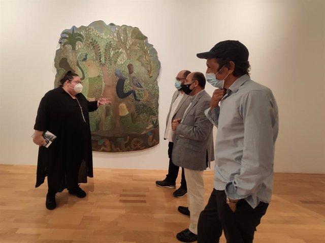 Responsables de la exposición 'Cantos de Griot' delante de una de las obras expuestas en el DA2 de Salamanca.
