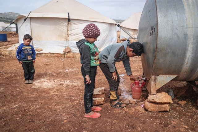 Archivo - 11 March 2021, Syria, Kafr Aruq: Syrian children bottle water from a water container at a refugee camp for internally displaced people in the village of Kafr Aruq. On Wednesday, UN Secretary-General Antonio Guterres has underlined that the Syria