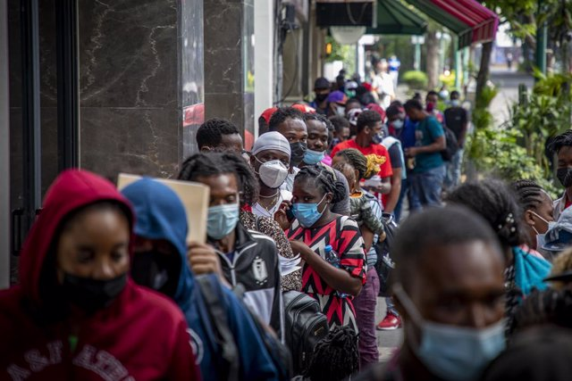 23 September 2021, Mexico, Mexico City: Migrants queue in front of the The Mexican Commission for Refugee Assistance office, where they want to apply for asylum. Migrants from Haiti have arrived in the Mexican capital from the south in the last three days