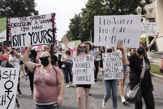 02 October 2021, US, Atlanta: Protesters hold placards as they march through downtown Atlanta during an abortion rights protest in Atlanta. Photo: John Arthur Brown/ZUMA Press Wire/dpa