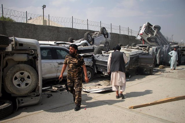 (210921) -- KABUL, Sept. 21, 2021 (Xinhua) -- Taliban members walk past damaged vehicles at the Kabul airport in Kabul, capital of Afghanistan, Sept. 20, 2021. The Kabul airport were damaged with its many facilities destroyed during the withdrawal of the