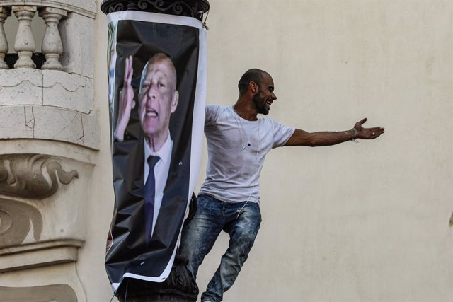 03 October 2021, Tunisia, Tunis: A man gestures as he climbs a light pole next to a poster bearing the image of Tunisian President Kais Saied during a protest supporting the latter, after he suspended parliament and assumed executive authority in July 202